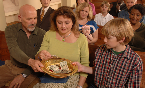 A Sunday morning church congregation putting money in the offering plate
