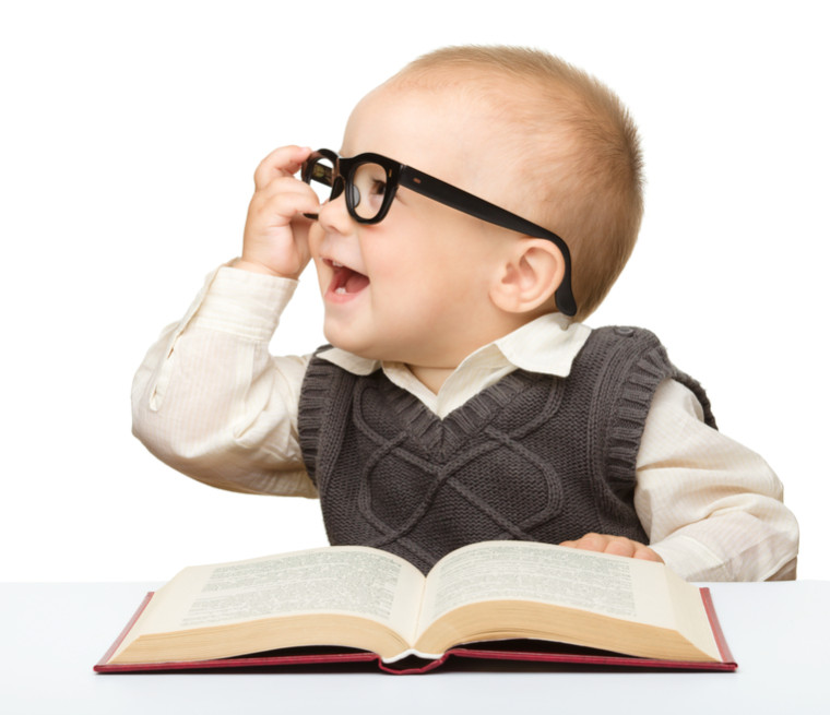 Cute little child play with book and glasses while sitting at table, isolated over white