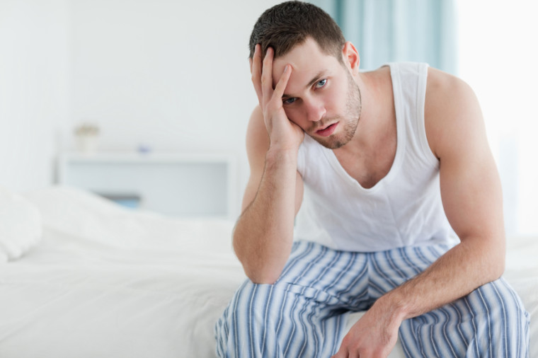 Depressed man sitting on his bed